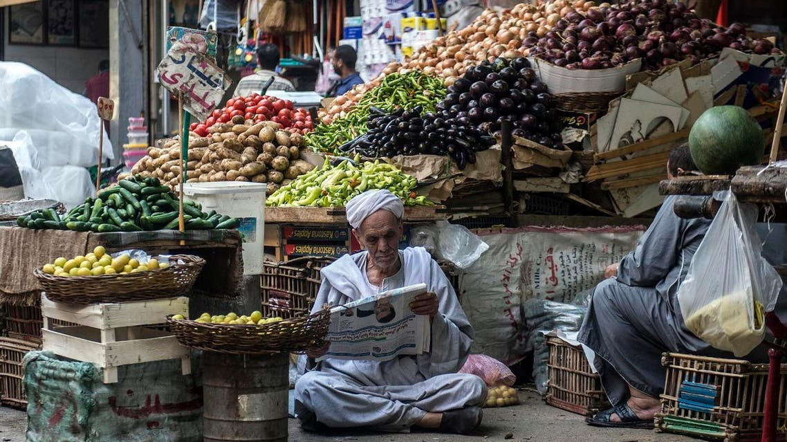 An Egyptian vendor reads the newspaper outside his fruit and vegetable stand in Egyptians in Cairo, on May 15, 2017. (AFP)