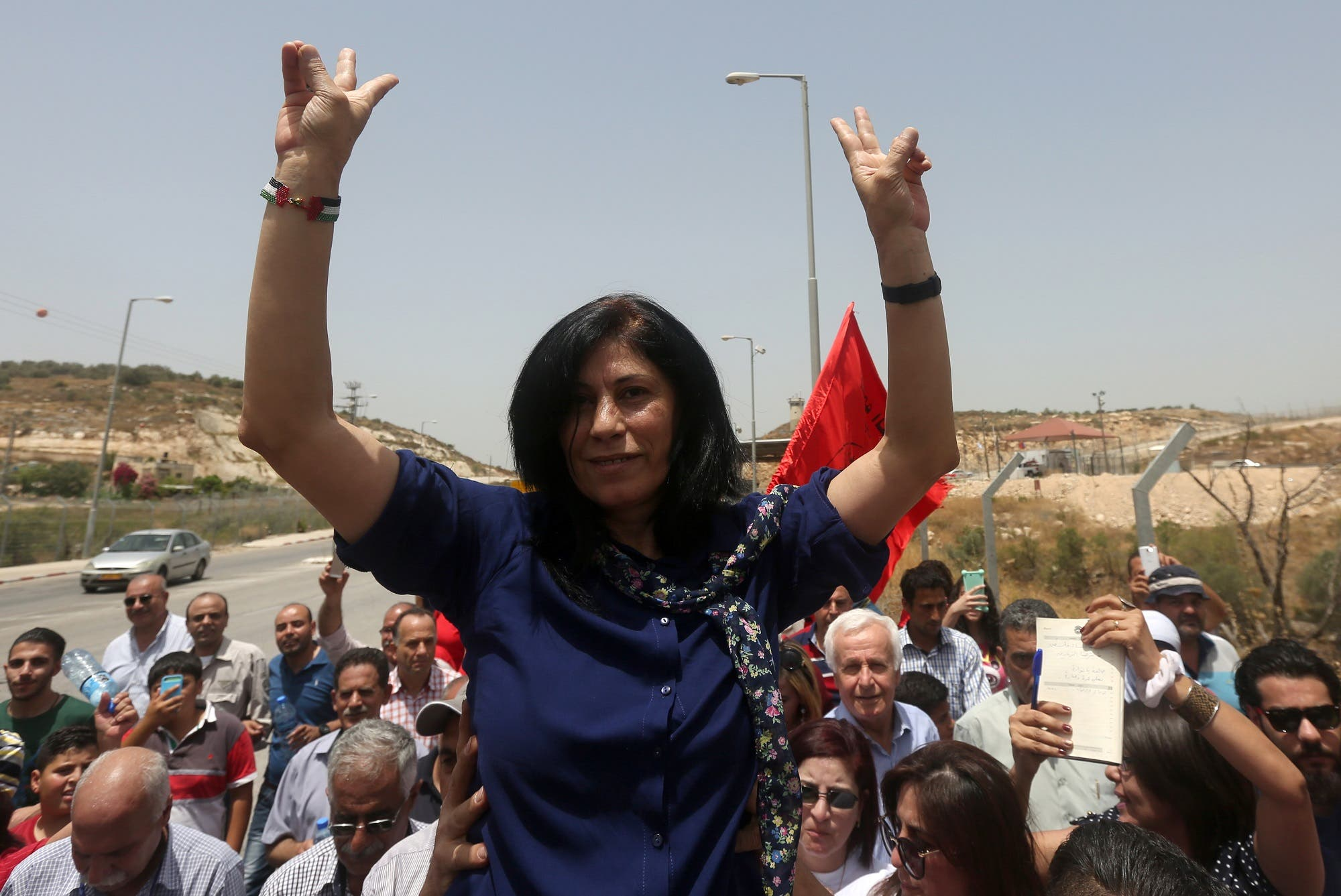 Khalida Jarrar flashes the sign for victory as she is lifted up by supporters at the Jubara checkpoint near the northern West Bank city of Tulkarem, following her release from an Israeli jail on June 3, 2016. (AFP)