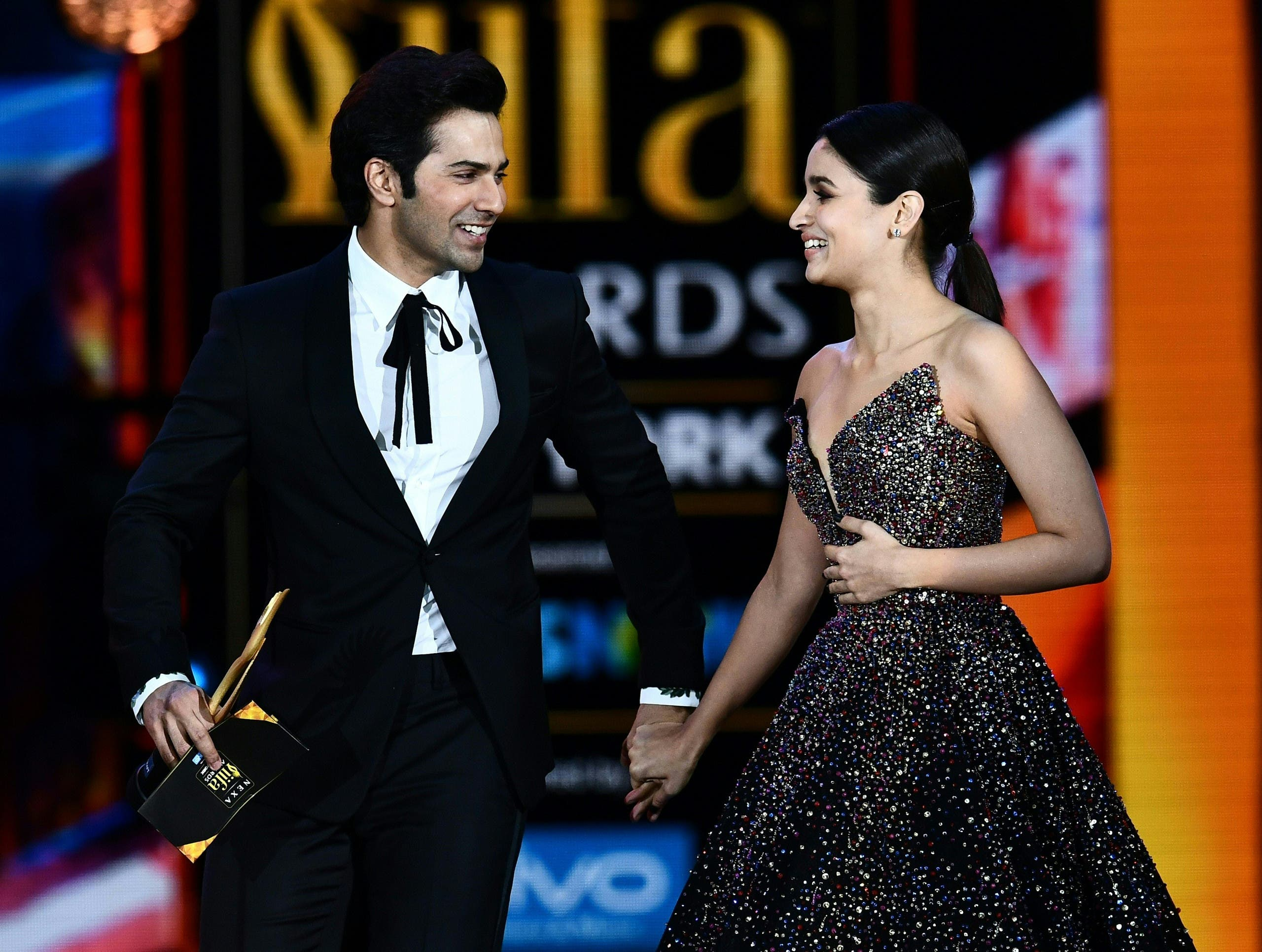 Alia Bhatt reacts after learning she got the award for Best Actress as she arrives with Varun Dhawan on stage during the IIFA Awards July 15, 2017 AFP