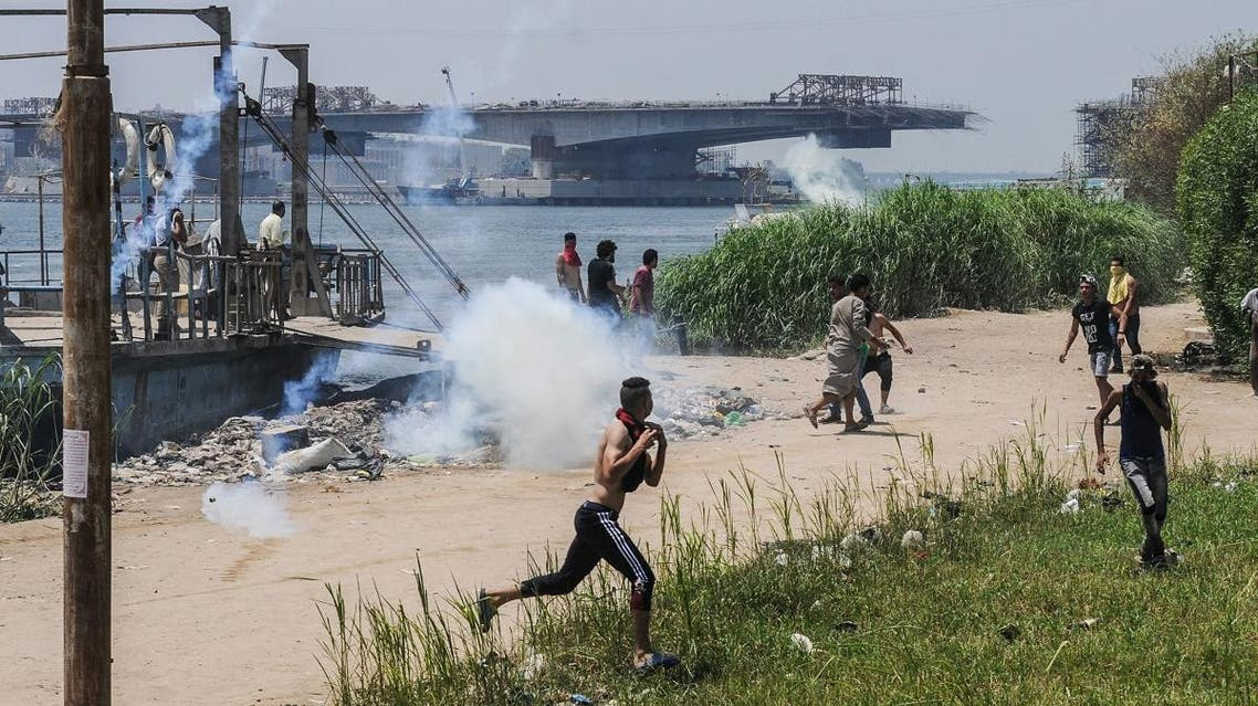 Egyptians run for cover from tear gas during clashes with security forces in the Nile island of Warraq in Giza province. (AFP)