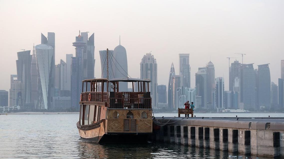 Boys take picture of a boat on the corniche in the Qatari capital Doha on July 2, 2017. (AFP)