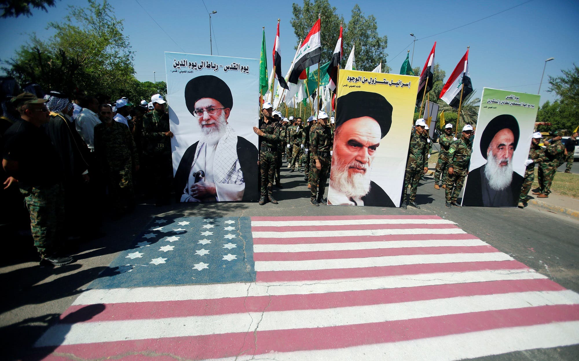 Members of Popular Mobilization hold portraits of Ayatollah Khomeini (C), Supreme Leader Ayatollah Ali Khamenei (L) and Iraq's top Shi'ite cleric Grand Ayatollah Ali al-Sistani during a parade marking the annual al-Quds Day in Baghdad on June 23, 2017. (Reuters)