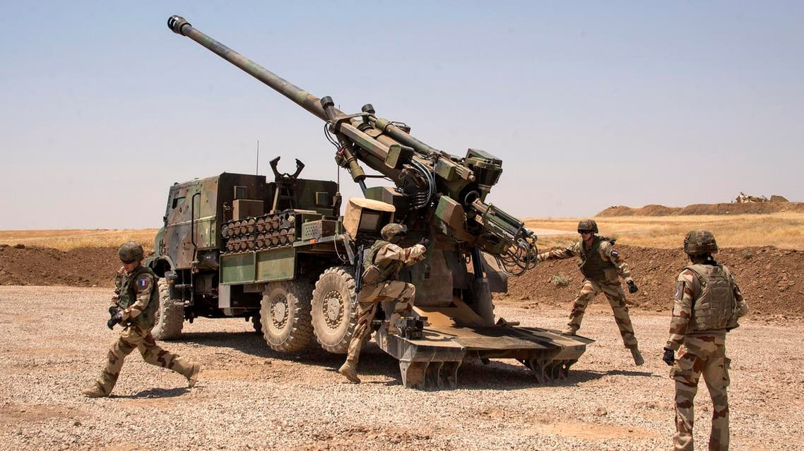 French soldiers from the Wagram Task Force stand next to a unit of CAESAR, a French self-propelled 155 mm howitzer, north of Mosul on July 13, 2017, as the French army provides military support for Iraq forces fighting the Islamic State (IS) group. The Iraqi prime minister Haider al-Abadi on July 10 declared Mosul finally retaken from the Islamic State group, which seized the city and swathes of other territory in 2014. (AFP)