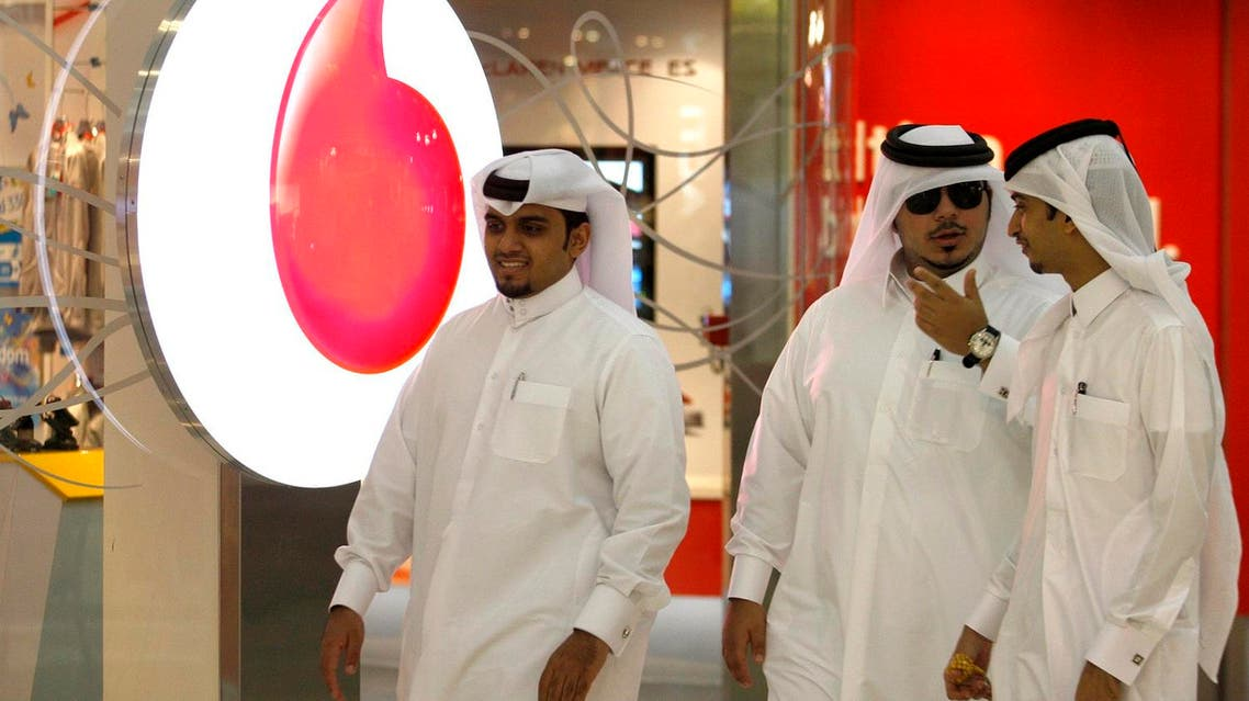 Men walk past a Vodafone-Qatar Telecommunication office in Doha on October 22, 2009. (Reuters)