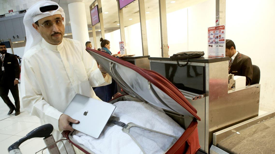 Kuwaiti social media activist Thamer al-Dakheel Bourashed puts his laptop inside his suitcase at Kuwait International Airport in Kuwait City before boarding a flight to the US on March 23, 2017. (AFP)