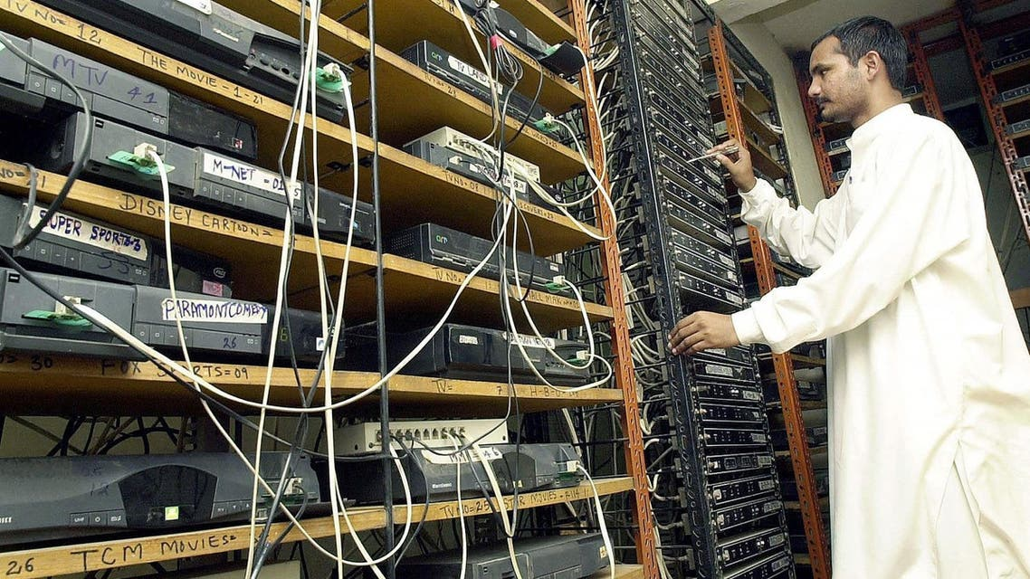 A Pakistani cable television operator unplugs a cable channel connection following a ban on Indian channels imposed by the Pakistani government in Karachi, 2 August 2003. (AFP)