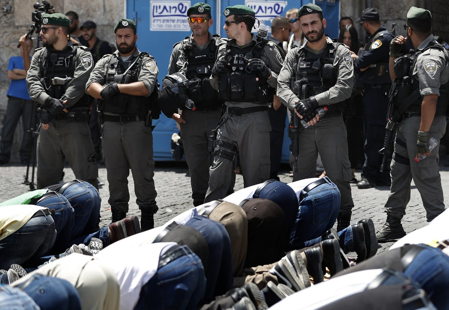 Israeli forces stand guard as Palestinian Muslim worshippers, who refuse to enter Al-Aqsa mosque compound due to newly-implemented security measures by Israeli authorities. (AFP)
