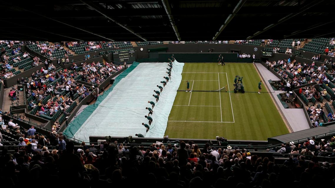 Ground staff pull the covers off following a rain delay at the All England Lawn Tennis Championships at Wimbledon, England, on June 26, 2012. (AP)