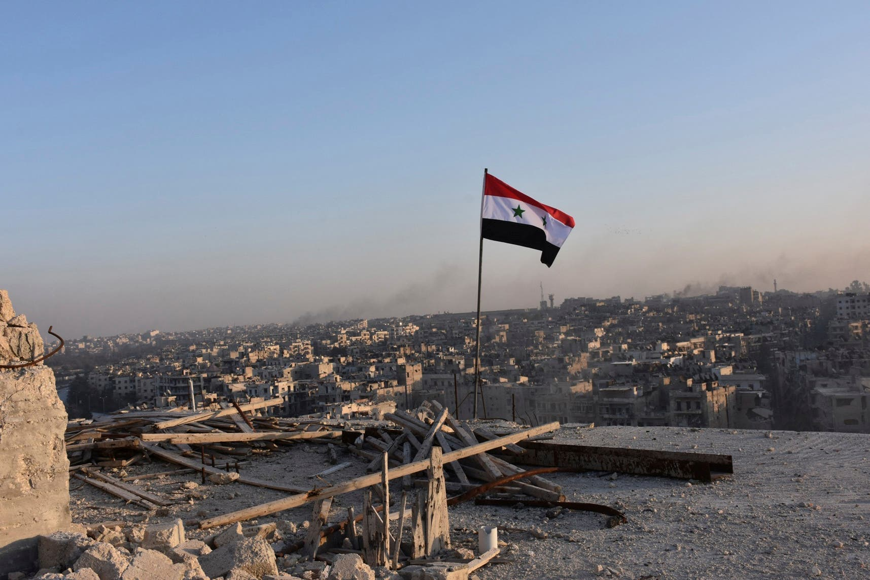 A Syrian national flag flutters near a general view of eastern Aleppo after Syrian government soldiers took control of al-Sakhour neigborhood in Aleppo. (Reuters)