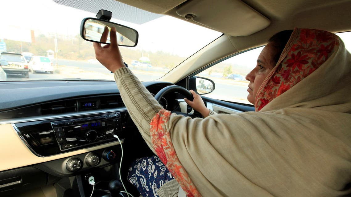 """Yasmin Perveen, one of the pioneer women """"captains"""" of Careem, adjusts back mirror while driving her car in Islamabad, Pakistan December 7, 2016. (Reuters)"""