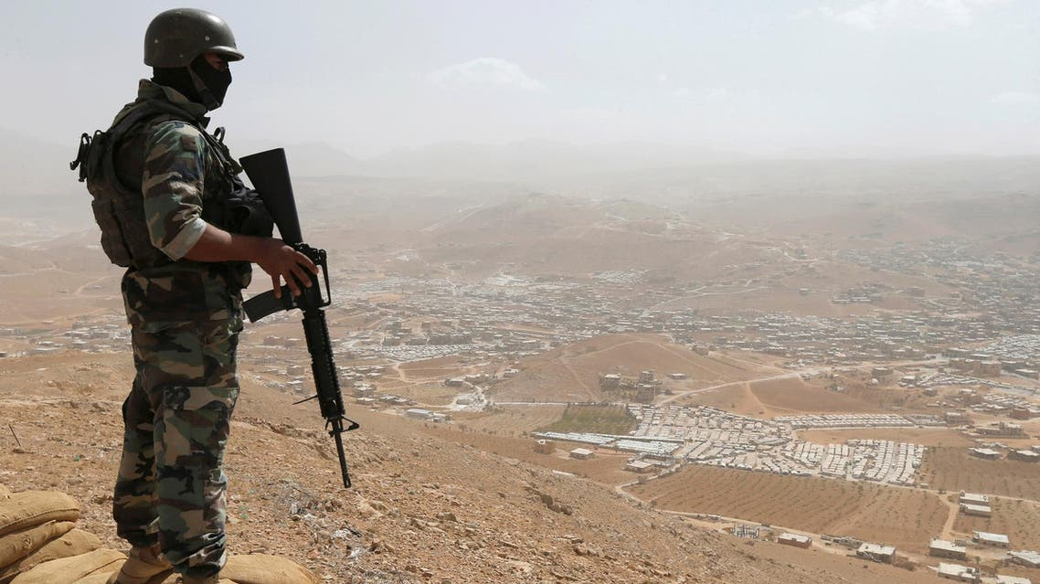 A Lebanese soldier carries his weapon as he stands on sandbags at an army post in the hills above the Lebanese town of Arsal on September 21, 2016. (Reuters)