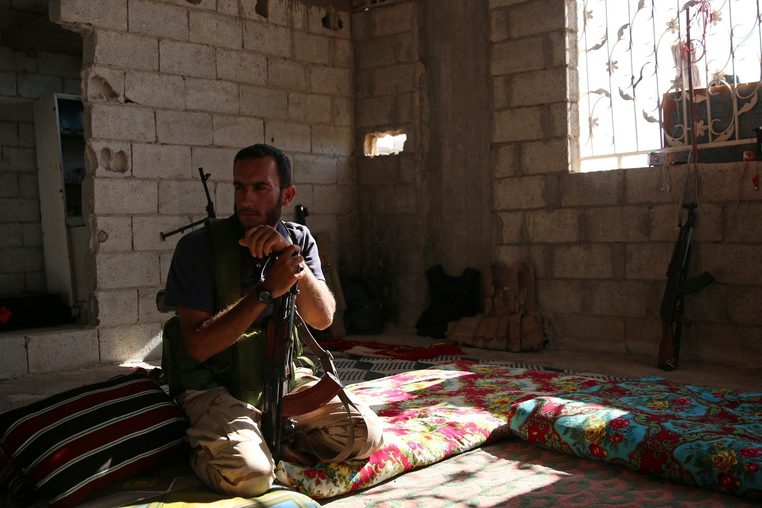 A Free Syrian Army fighter holds his weapon inside a house in rebel-held Al-Yadudah village, in Deraa Governorate, Syria, July 19, 2017. (Reuters)