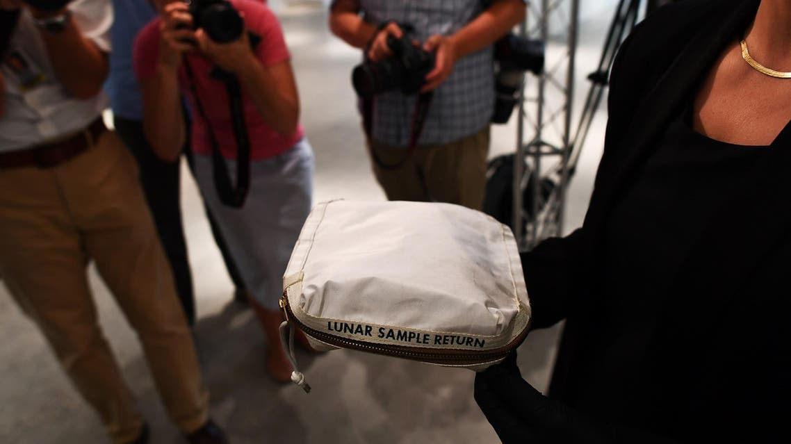 Sotheby's Cassandra Hatton displays the Apollo 11 Contingency Lunar Sample Return Bag, used by Neil Armstrong on Apollo 11 to bring back the very first pieces of the moon ever collected, during a media preview for Space Exploration auction in New York on July 13, 2017. (AFP)