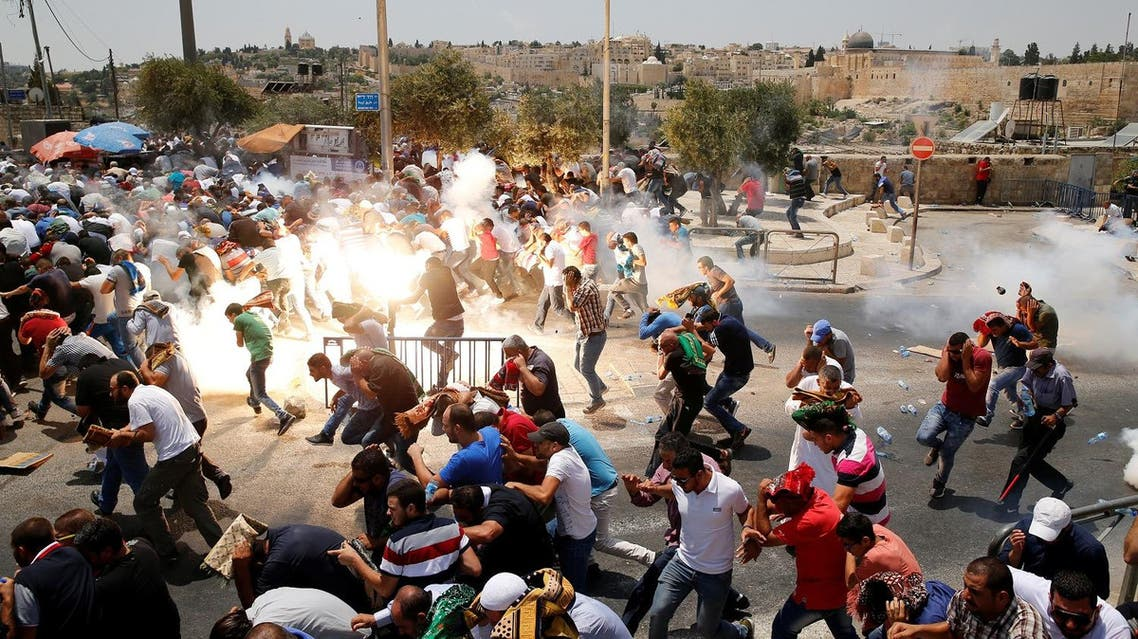 Palestinians react following tear gas that was shot by Israeli forces after Friday prayer on a street outside Jerusalem's Old city July 21, 2017. (Reuters)