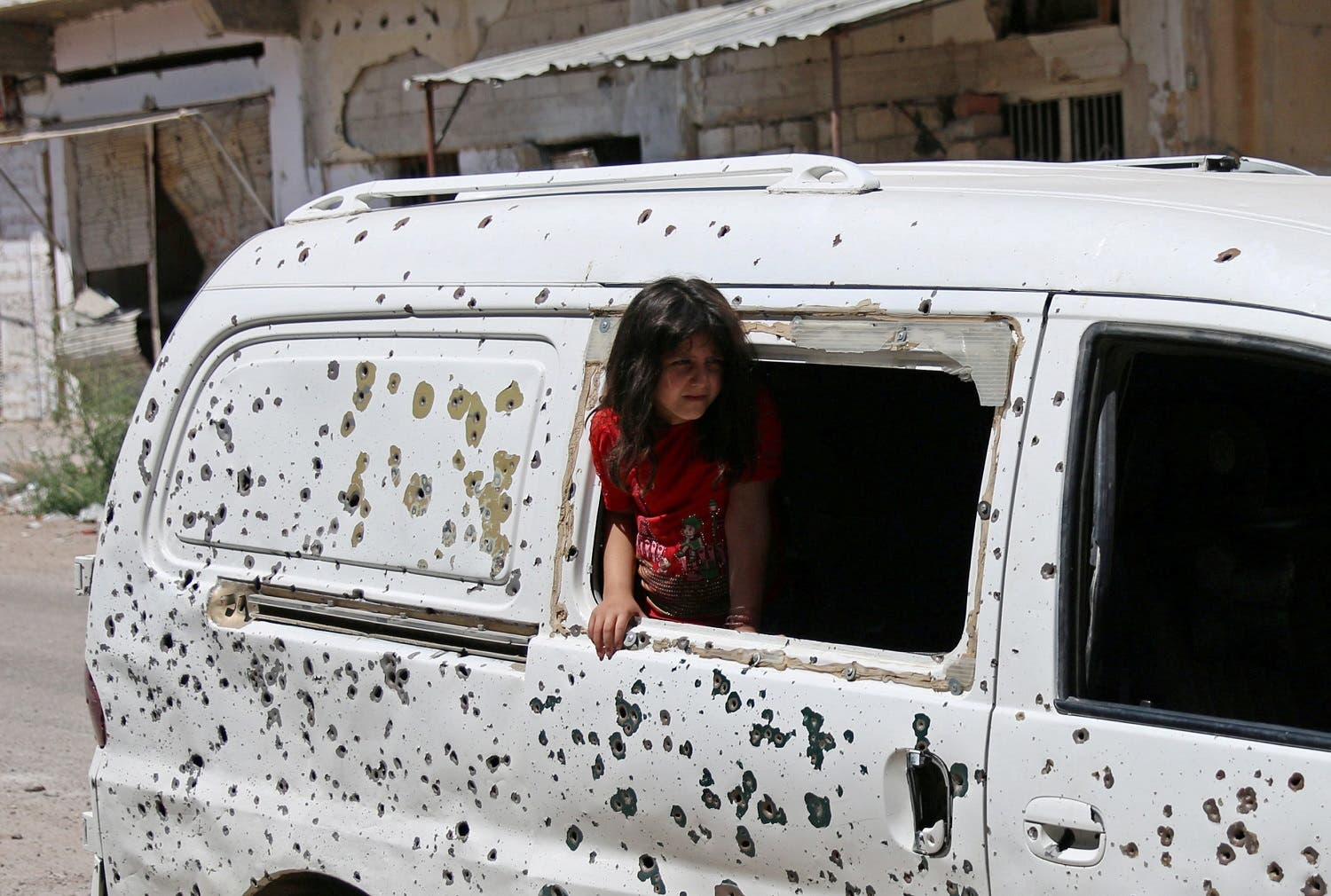 A girl looks out from a bullet-riddled bus in a rebel-held part of the southern city of Deraa, Syria July 9, 2017. (Reuters)