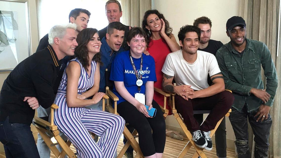 """Sydney Lang, 16, of Edmonton, Alberta, seated center, poses with cast members from """"Teen Wolf"""" during a meet-and-greet arranged by the Make-A-Wish Foundation on Friday, July 21, 2017, in San Diego. (AP)"""
