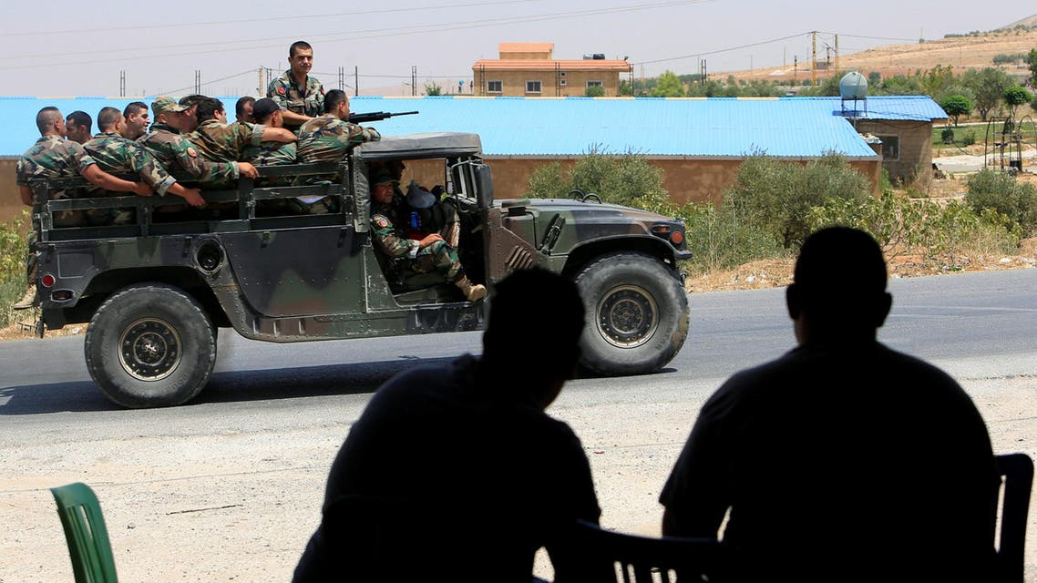 People watch as Lebanese army soldiers patrol a street in Labwe, at the entrance of the border town of Arsal, in Bekaa Valley, Lebanon July 22, 2017.
