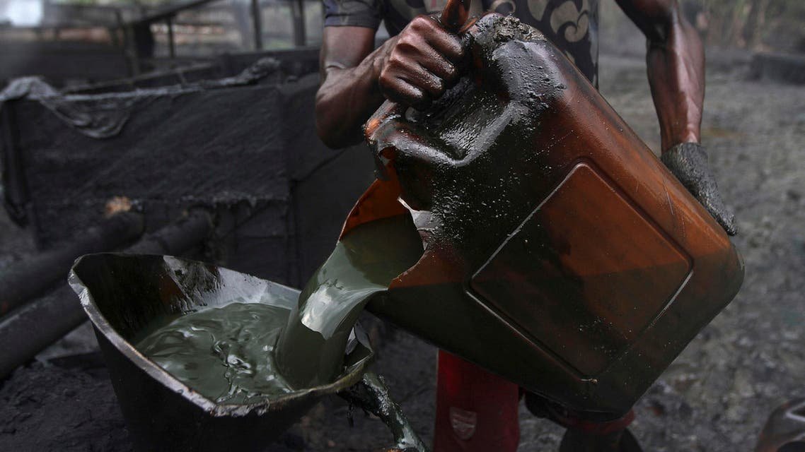 A worker pours crude oil into a locally made burner using a funnel at an illegal oil refinery site near river Nun in Nigeria's oil state of Bayelsa November 25, 2012.reuters