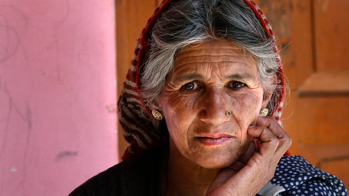 In this Dec. 15, 2013 photograph, Bijaya Devi, 64, the oldest widow of the village stands at her house at the Deoli-Benigram village in Rudraprayag district, in the northern state of Uttarakhand, India.
