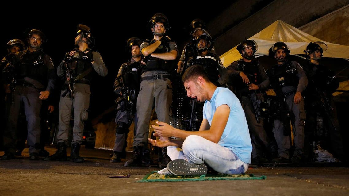 Israeli border police stand guard as a Palestinian man takes part in evening prayers outside the Lion's Gate of Jerusalem's Old City on July 23, 2017. (Reuters)