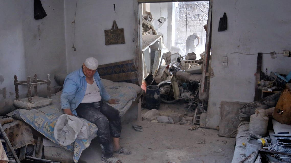 A Syrian man sits in his damaged house on July 25, 2017 following an air strike late the previous night on the rebel-held town of Arbin, east of the capital. Women and children were among the dead in the 11:30 pm (2030 GMT) strike on Arbin in the Eastern Ghouta rebel enclave where the government declared a ceasefire on July 22, the Syrian Observatory for Human Rights said.