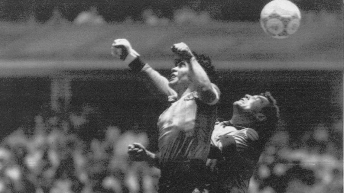 """FILE - In this June 22, 1986 file photo Argentina's Diego Maradona, left, beats England goalkeeper Peter Shilton to a high ball and scores his first of two goals in a World Cup quarterfinal soccer match, in Mexico City. On this day: This was the day of the """"Hand of God,"""" when Maradona used his left fist to knock a ball past England's Shilton. (AP Photo/El Grafico, Buenos Aires, File)"""