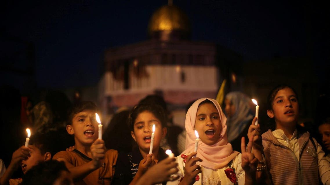 Palestinian children hold candles during a protest against Israel's newly-installed security measures at the entrance to the al-Aqsa mosque compound, in Khan Younis in the southern Gaza Strip July 23, 2017. REUTERS/Ibraheem Abu Mustafa