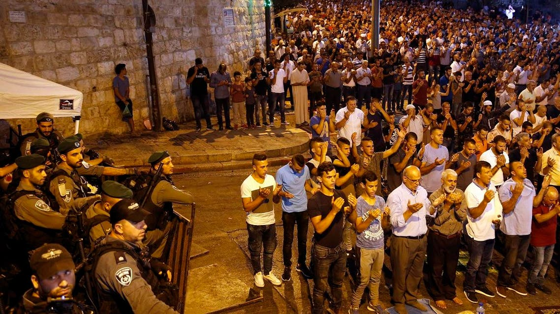 Israeli security forces stand by as Palestinian Muslim worshippers pray outside Lions' Gate, a main entrance to the Al-Aqsa mosque compound. (AFP)