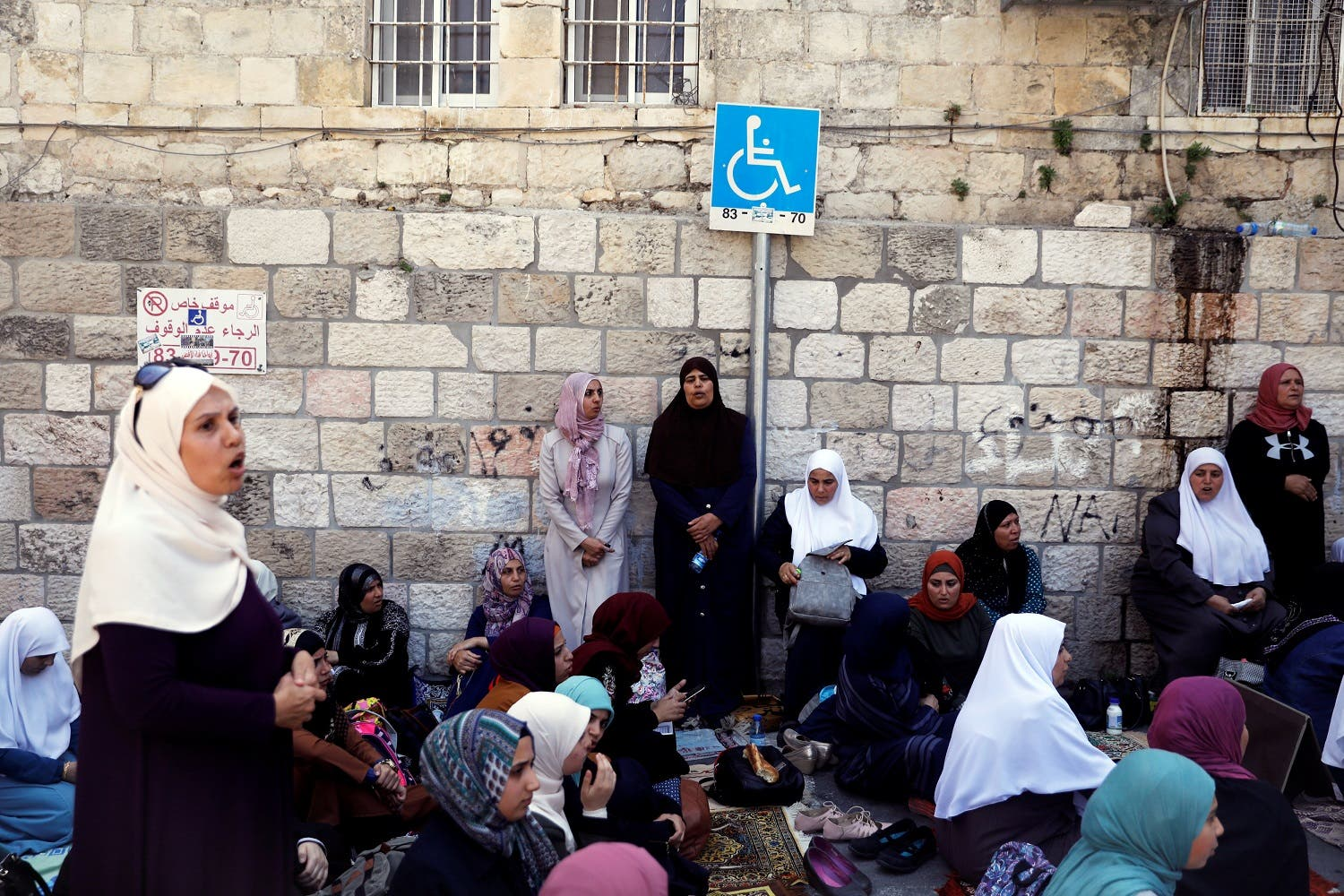 Palestinian women shout slogans as they sit outside the compound in Jerusalem's Old City on July 25, 2017. (Reuters)