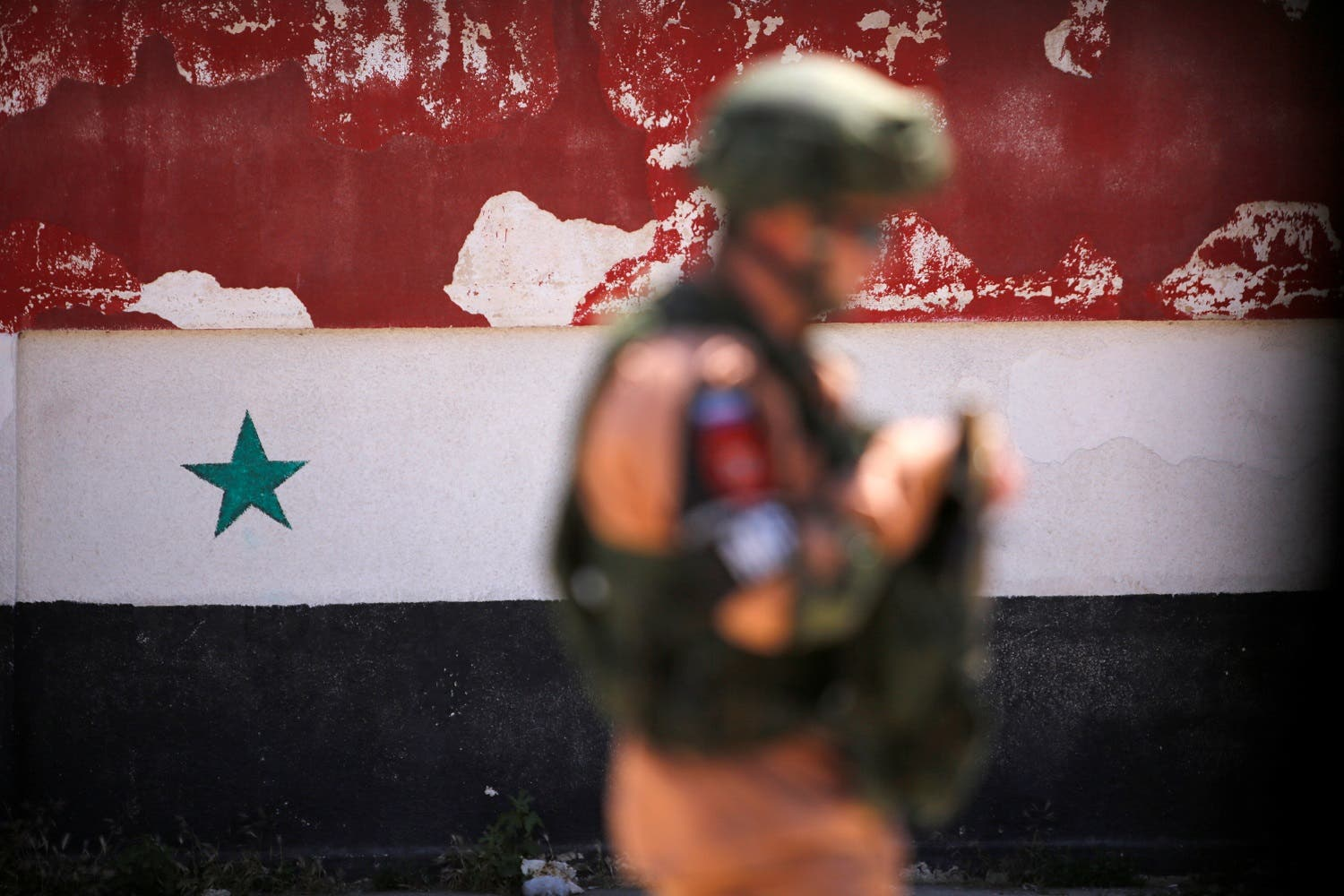 A Russian soldier stands guard near a Syrian national flag, Syria May 21, 2017. (Reuters)