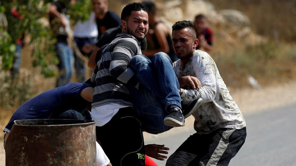 A wounded Palestinian man is evacuated during clashes with Israeli troops in the West Bank village of Khobar near Ramallah on July 22, 2017. (Reuters)