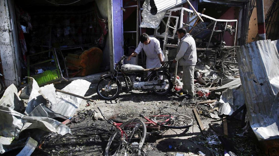Men look at the remains of their properties at the site of a suicide attack in Kabul, Afghanistan. (AP)