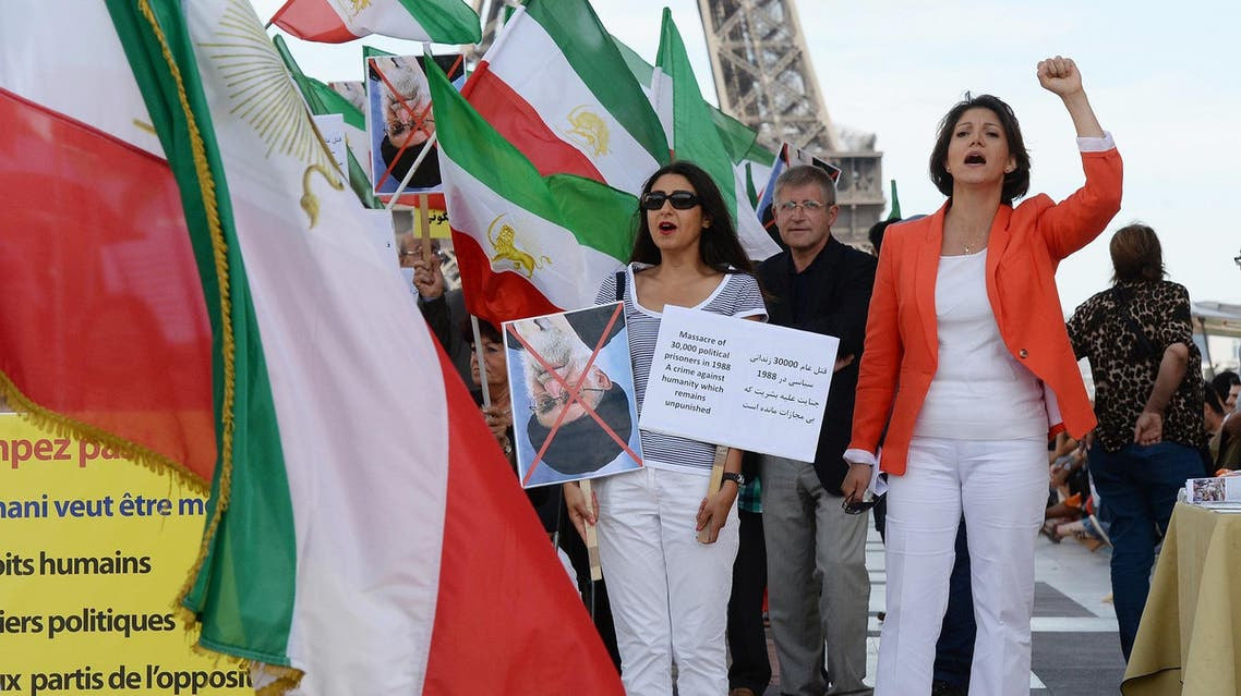 People chant slogans and hold pre-revolutionary Iranian flags in Paris, on August 17, 2013, as they take part in a rally marking the 25th anniversary of the 1988 massacre of Iranian political prisoners. (AFP)