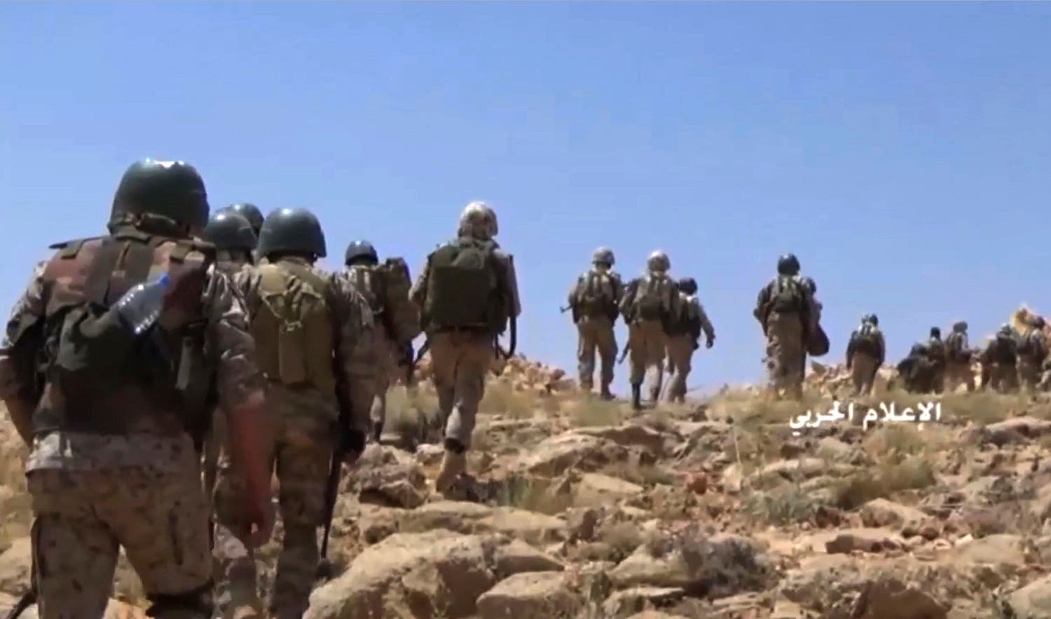 This frame grab from video released on July 22, 2017 shows Hezbollah fighters advancing up a hill during clashes with al-Qaeda-linked militants in an area on the Lebanon-Syria border. (AP)