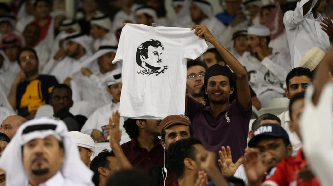 A man holds a t-shirt with a picture of Qatar's Emir Sheikh Tamim Bin Hamad Al-Thani on June 13, 2017. (Reuters)