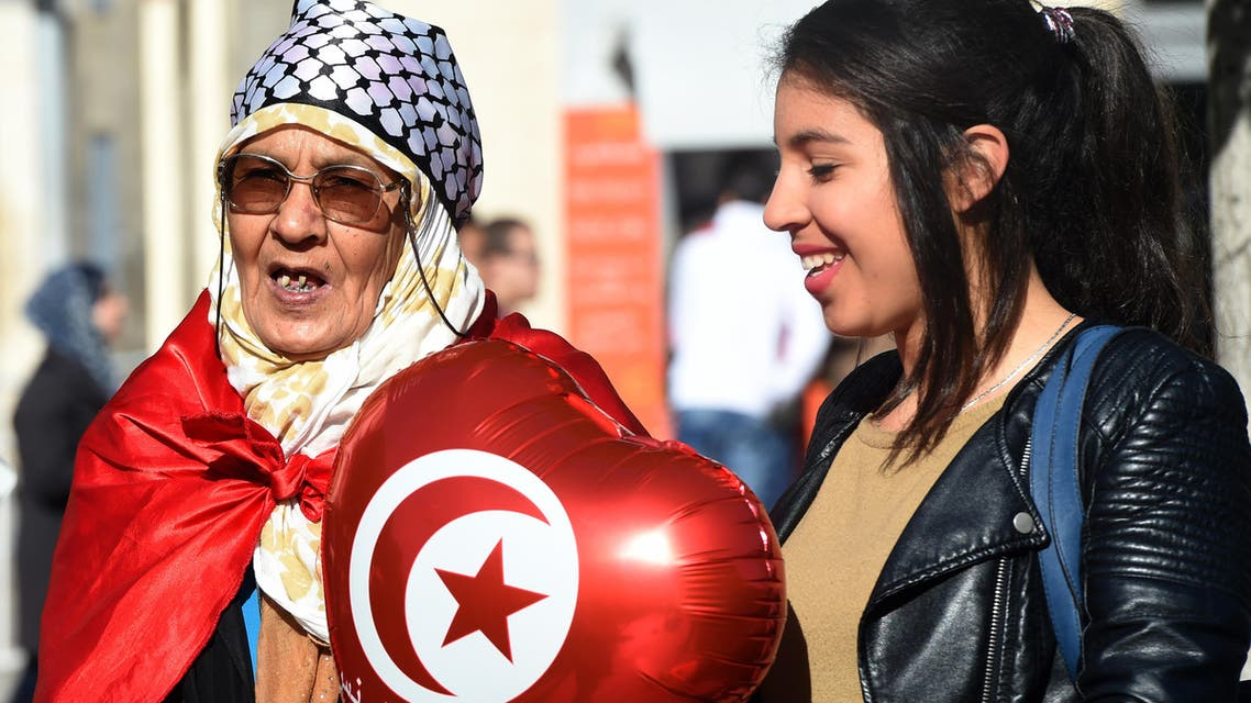 Tunisian women hold a ballon with their national flag during a rally on January 14, 2016 in the Habib Bourguiba Avenue in the capital Tunis to mark the fifth anniversary of the 2011 revolution. AFP