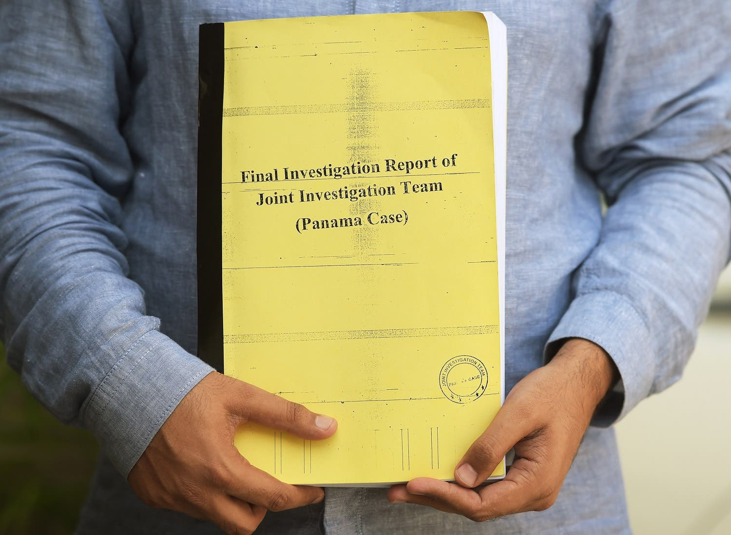 A Pakistani journalist poses for a photograph with a copy of a corruption report released by JIT in Islamabad on July 12, 2017. (AFP)