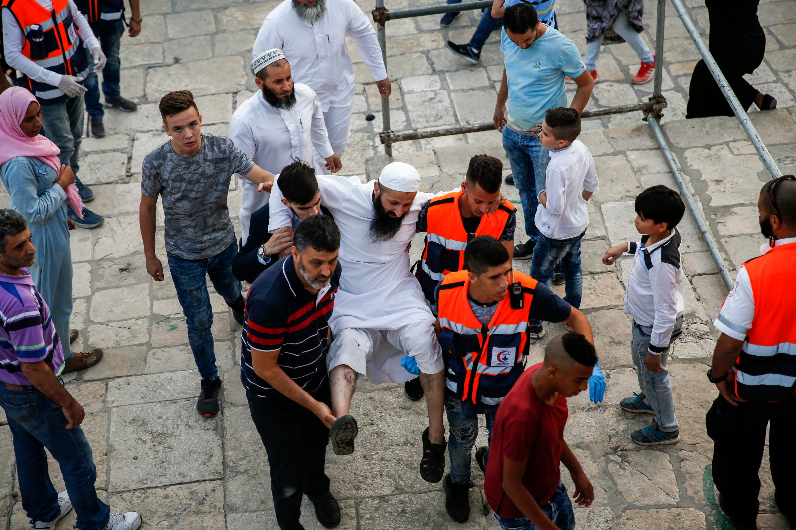 Palestinian paramedics carry an injured man after clashes broke out inside the Al-Aqsa mosques compound in Jerusalem's Old City on July 27, 2017. afp
