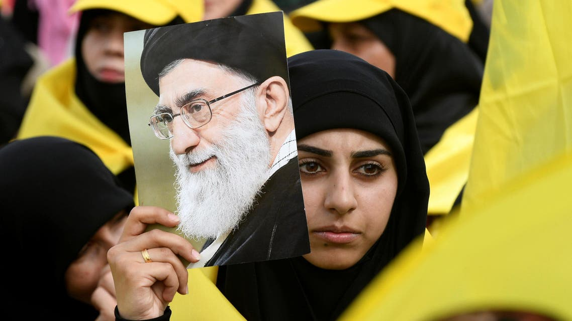 A woman carries a picture of Iran's Supreme Leader Ayatollah Ali Khamenei as she watches Lebanon's Hezbollah leader Sayyed Hassan Nasrallah appear on a screen during a live broadcast to speak to his supporters at an event marking Resistance and Liberation Day, May 25, 2017. (Reuters)