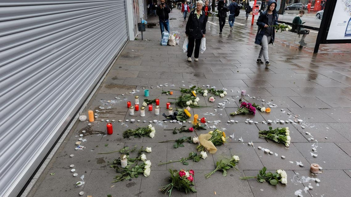 A makeshift memorial of flowers and candles arranged like a peace sign in Hamburg, northern Germany, at the site where a man killed one person and wounded several others in a knife attack the day before. (AFP)