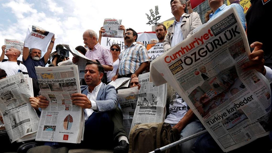 Press freedom activists read Cumhuriyet during a protest in solidarity with the jailed members of the newspaper outside a courthouse in Istanbul. (Reuters)