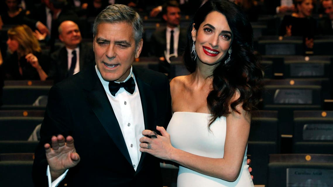 Actor George Clooney and his wife Amal pose before the start of the 42nd Cesar Awards ceremony in Paris, France, February 24, 2017. REUTERS/Philippe Wojazer