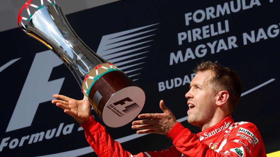 Ferrari's Sebastian Vettel celebrates winning the Hungarian Grand Prix on the podium with the trophy.  (Reuters)