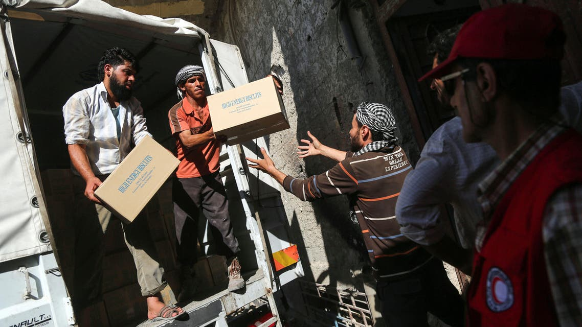 A picture taken on July 30, 2017 shows aid packages from the United Nations and the Syrian Arab Red Crescent (SARC) being delivered to locals in the rebel-held town of Nashabiyah in eastern Ghouta for the first time in five years. AMER ALMOHIBANY / AFP