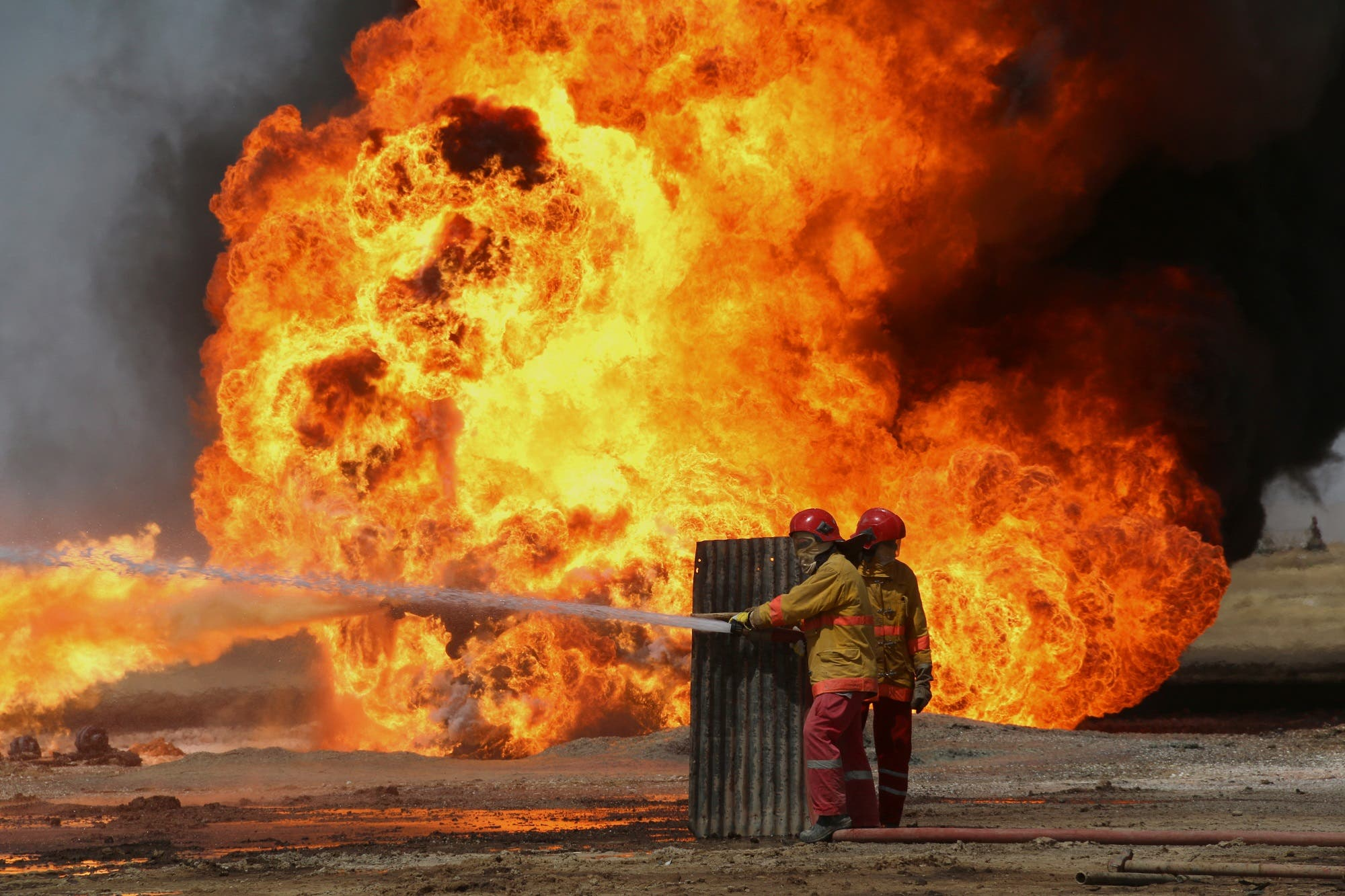 Oil workers and firemen try to extinguish flames at the Khabbaz oil field some 20 km away from Kirkuk on June 1, 2016 following an attack by ISIS. (AFP)