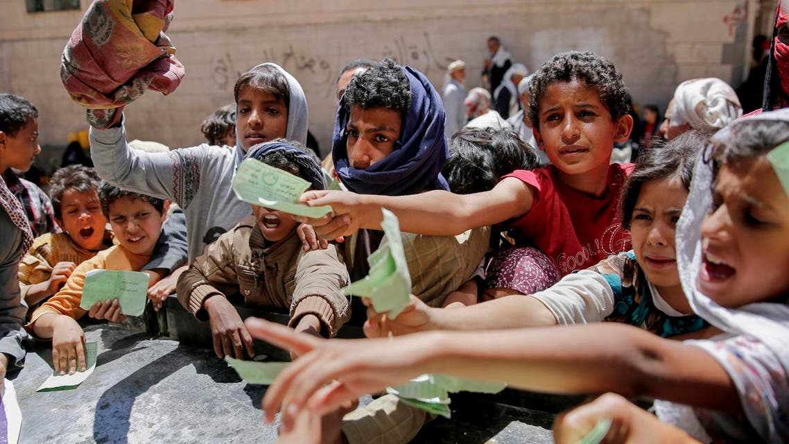 Yemenis present documents in order to receive food rations provided by a local charity, in Sanaa, Yemen. (AP)