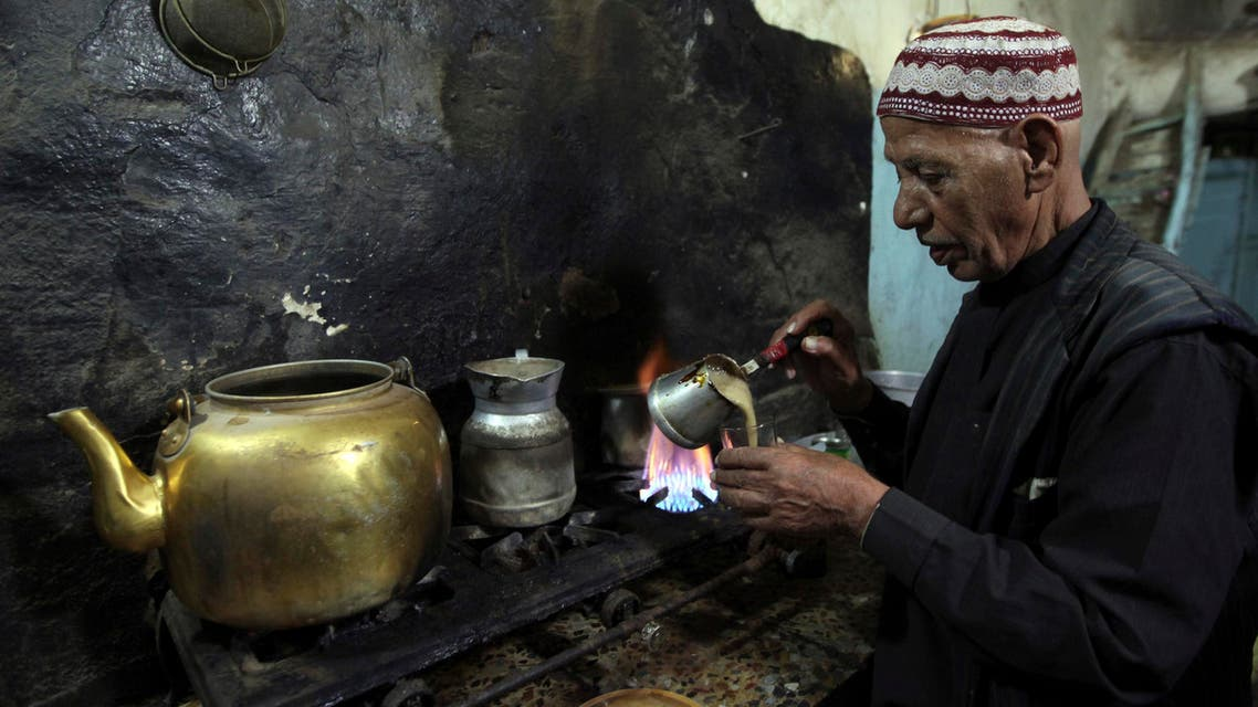 A vendor pours coffee into a cup for customers inside his cafe in the old city of Al-Masnaah in Al-Mahaweet, around 110 km (68 miles) north west of capital Sanaa June 27, 2013. REUTERS/Mohamed al-Sayaghi