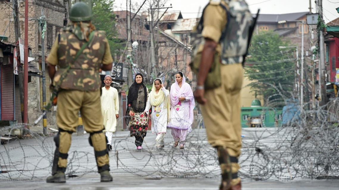 Indian paramilitary troopers stand guard as pedestrians walk along a road during restrictions after Kashmiri separatists called for a one-day strike to protest a civilian killing in Srinagar on August 2, 2017. (AFP)