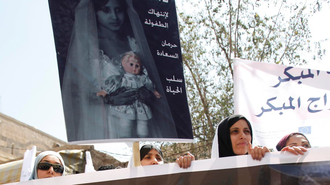 Yemeni women hold up a poster portraying a child bride during a sit-in outside the parliament in Sanaa March 23, 2010. reuters