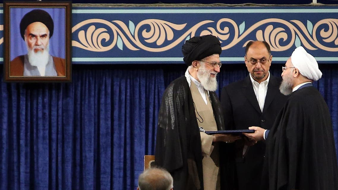 A handout picture released by the official website of the Iranian supreme leader Ayatollah Ali Khamenei shows him (L) giving his official seal of approval during the swearing in ceremony of President Hassan Rouhani (R) to serve his second term, as deputy chief of supreme leader's office Vahid Haghanian (C) looks on in Tehran on August 3, 2017.  HO / IRANIAN SUPREME LEADER'S WEBSITE / AFP